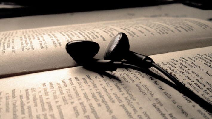 Fones de ouvido em cima de um livro aberto