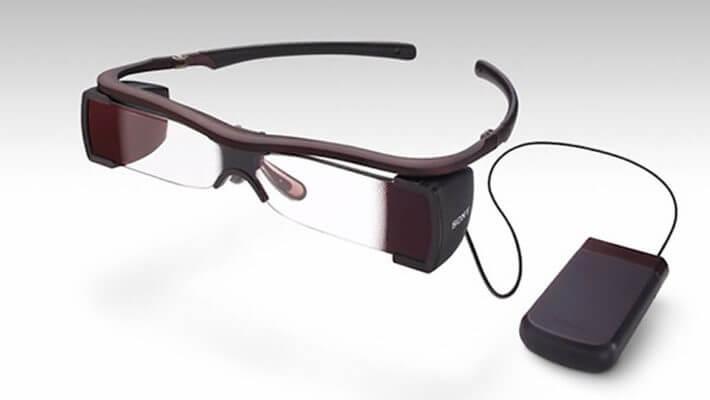 Em uma superfície cinza, óculos que exibe legendas na lente, ao lado aparelho para recepção de audiodescrição