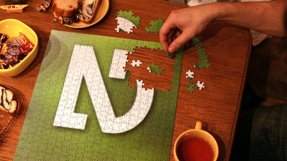 Sobre uma mesa um quebra-cabeça sendo montado. Na mesa há tigelas com doces, torradas e bebidas. O quebra-cabeça está quase pronto, faltando ser encaixado algumas peças no canto superior direito. O desenho do quebra-cabeça é o logotipo do leitor de tela NVDA