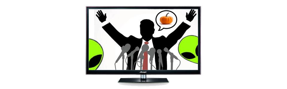 Um político de braços abertos, dando uma entrevista e pensando em abóboras; no canto inferior aparecem duas cabeças de alienígenas