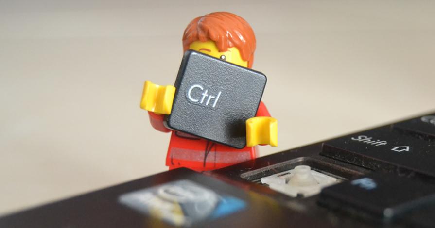 Foco em um teclado sem a tecla CTRL . Ao lado do teclado há um boneco segurando a tecla CTRL