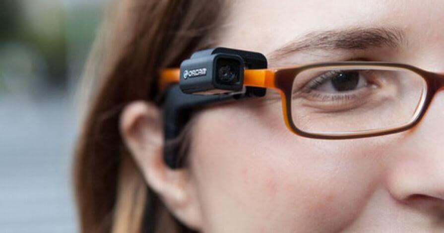 Em foco uma mulher de óculos. Na haste direita do óculos está acoplado o dispositivo orcam myeye