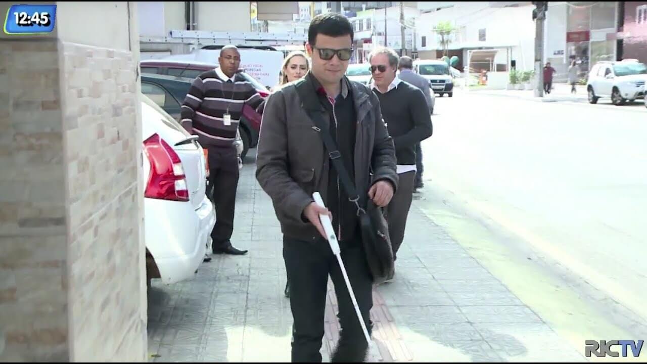 Uma pessoa com deficiência visual andando de bengala nas ruas de floriaanópolis