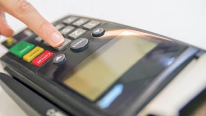 Close de um dedo apertando número três de uma maquininha de cartão