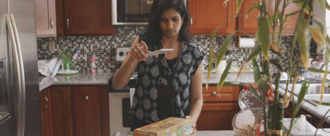 Mulher apontando smartphone para uma embalagem de produto