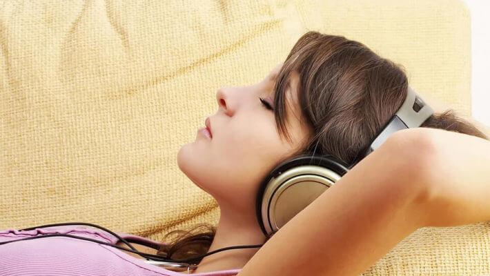Mulher deitada no sofá, de olhos fechados e fone de ouvido