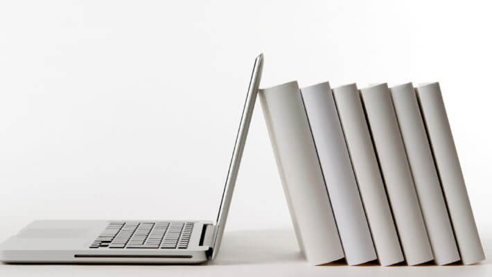 Livros apoiando um notebook