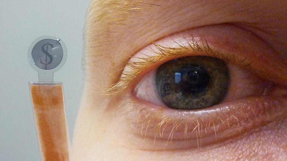 Foco em olho observando uma lente de contato