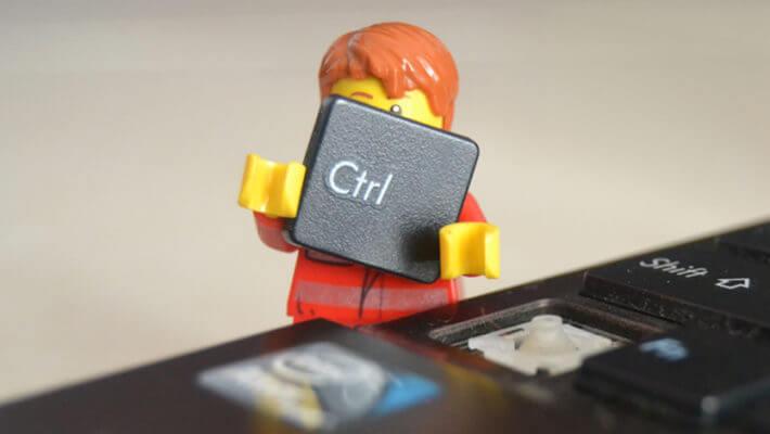 Um boneco lego segurando a tecla control de um teclado de notebook
