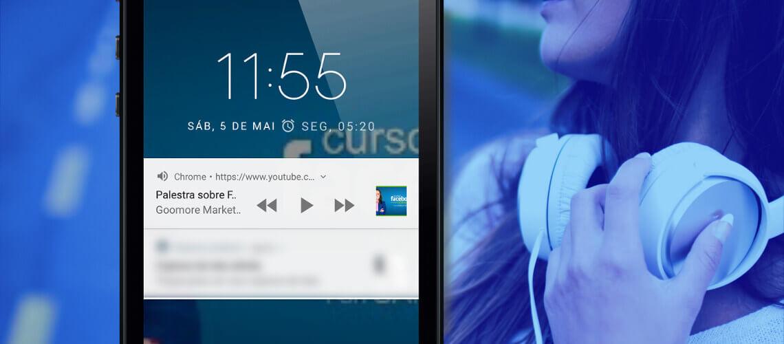 Em primeiro plano à esquerda, celular com tela bloqueada e controles de mídia, reproduzir, pausar e etc. Em segundo plano à direita, mulher com fone de ouvido de arco no pescoço