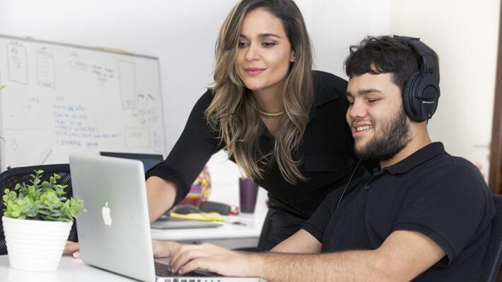 Mulher e jovem estão em frente ao computador. Ela, Paula Pedroza, criadora da Audima, veste roupa preta e sorri levemente. Ele, Lucas Tito, analista de negócios, é cego, veste camisa preta e está sorrindo, com fones nos ouvidos