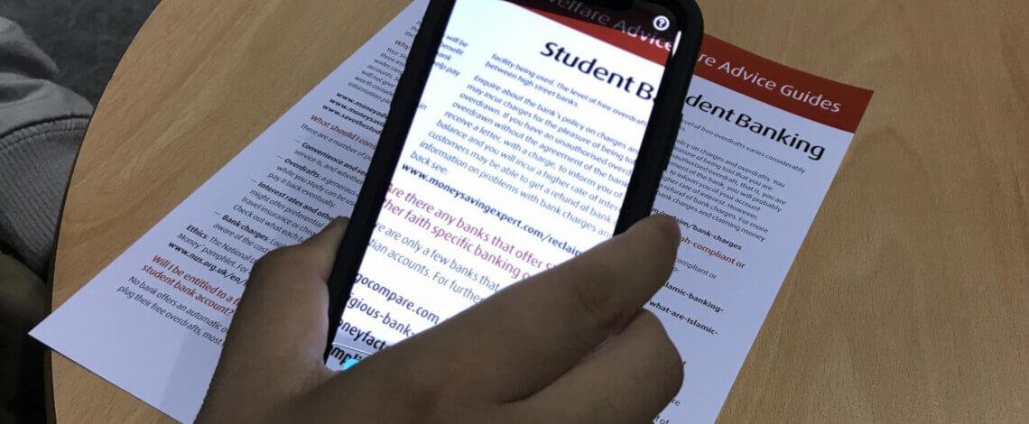 Close em mão segurando um celular apontando sua camêra para um texto impresso