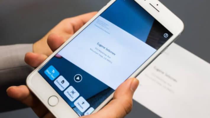 Close em um smartphone fazendo o reconhecimento de um texto sob uma mesa em segundo plano