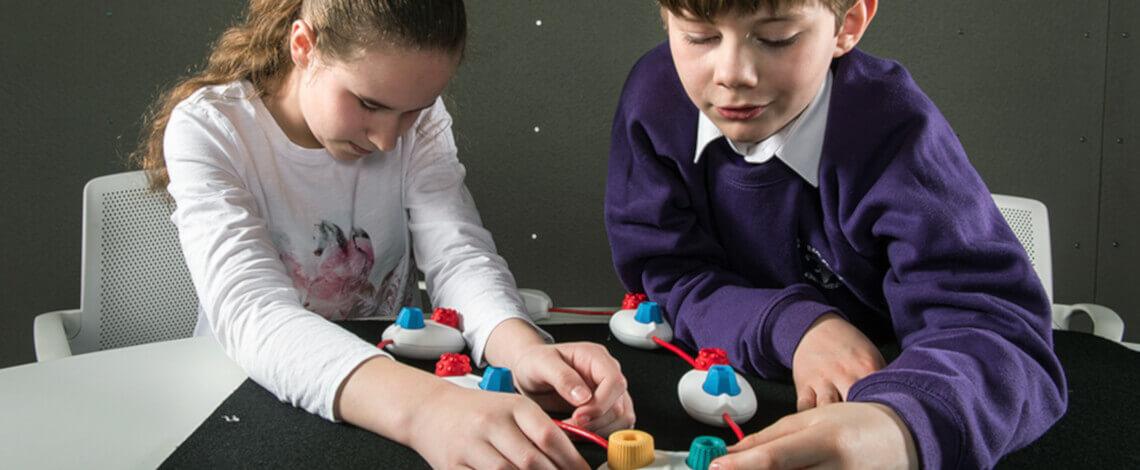 Duas crianças, co idade entre 7 e 11 anos, utilizando blocos táteis de programação
