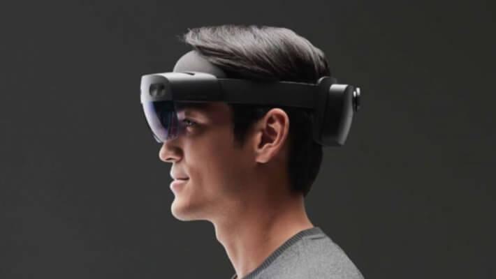 Uma pessoa, de perfil, utilizando o óculos de realidade virtual e aumentada HoloLens da Microsoft