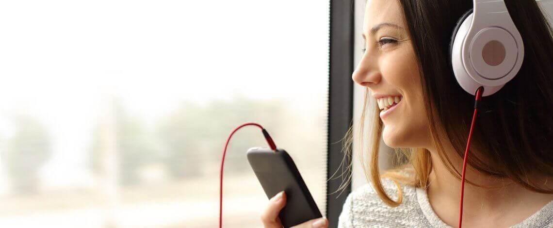 Perfil de mulher sorridente, com fones de ouvido e celular na mão